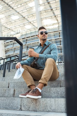 Photo for Low angle view of man in sunglasses holding coffee to go and business newspaper while sitting on stairs - Royalty Free Image