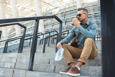 handsome man in sunglasses holding business newspaper and drinking coffee from paper cup while sitting on stairs
