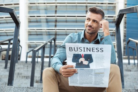 pensive smiling man holding business newspaper and looking away while sitting on stairs