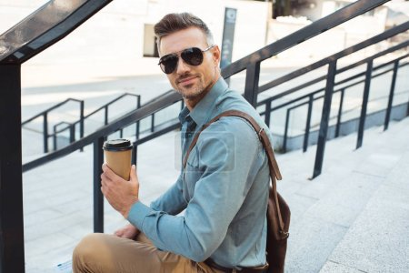 Photo for Handsome smiling middle aged man in sunglasses sitting on stairs and holding coffee to go - Royalty Free Image