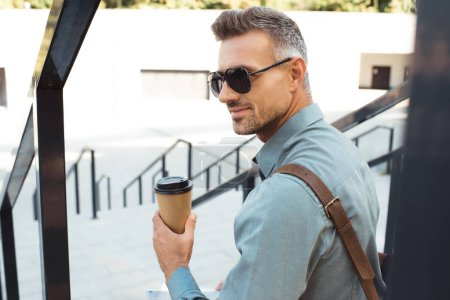 handsome smiling man in sunglasses holding coffee to go and sitting on stairs