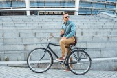 handsome man in sunglasses sitting on bicycle with coffee to go and looking over shoulder on street
