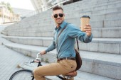handsome smiling man holding coffee to go and riding bike on street