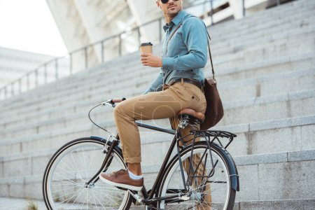 Photo for Cropped shot of man in earphones sitting on bike and holding disposable coffee cup on street - Royalty Free Image
