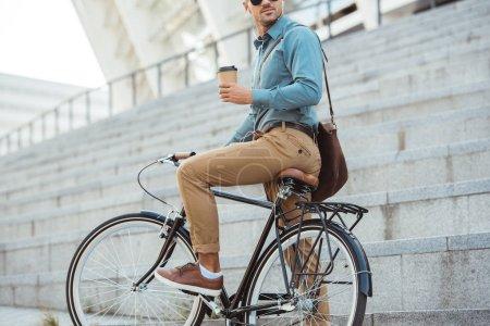 Photo pour Recadrée tir de l'homme dans les écouteurs assis sur le vélo et la tenue de tasse à café jetable sur la rue - image libre de droit