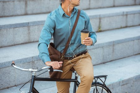 Photo pour Recadrée tir de l'homme dans les écouteurs tenant la tasse de papier et assis sur le vélo - image libre de droit