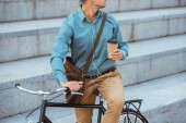 cropped shot of man in earphones holding paper cup and sitting on bicycle