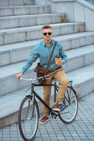 Photo for Handsome man in sunglasses holding coffee to go and looking at camera while sitting in bike on street - Royalty Free Image