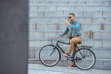 Foto de Hombre guapo bicicleta y beber de la taza de papel en la calle - Imagen libre de derechos