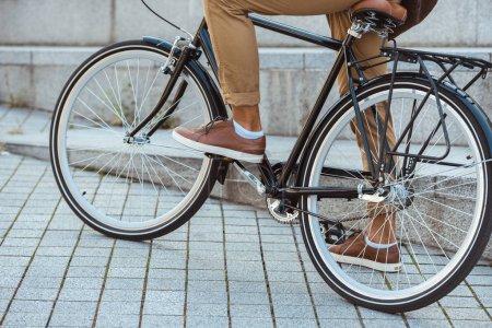 Photo pour Recadrée tir d'homme en bicyclette sur la rue - image libre de droit