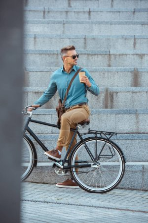 Photo for Stylish man in earphones and sunglasses holding paper cup and riding bicycle on street - Royalty Free Image