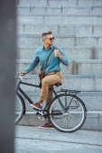stylish man in earphones and sunglasses holding paper cup and riding bicycle on street