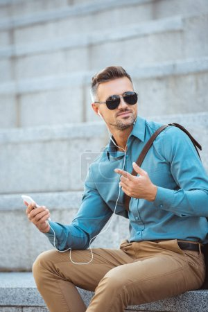 Photo for Handsome middle aged man in earphones sitting on stairs and using smartphone - Royalty Free Image