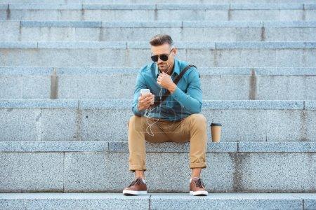 Photo pour Chic homme âgé moyen écouteurs assis dans les escaliers et à l'aide de smartphone - image libre de droit
