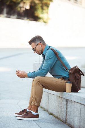 side view of man in earphones and sunglasses sitting on stairs and using smartphone
