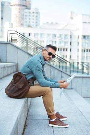 Photo for Side view of stylish man in sunglasses holding newspaper and looking at camera - Royalty Free Image