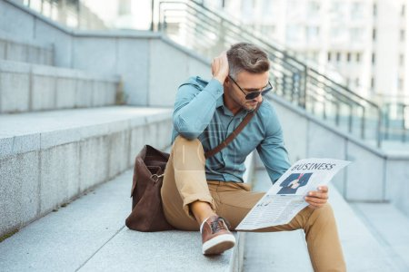 stylish middle aged man sitting on stairs and reading business newspaper