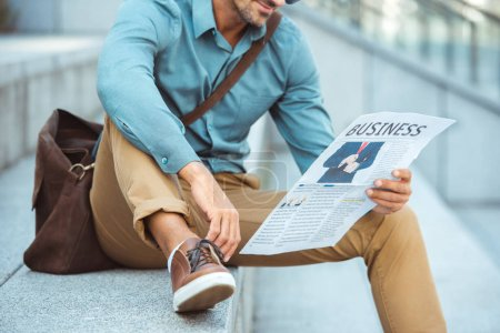 Photo pour Photo recadrée de l'homme assis dans les escaliers et lire le journal d'affaires - image libre de droit