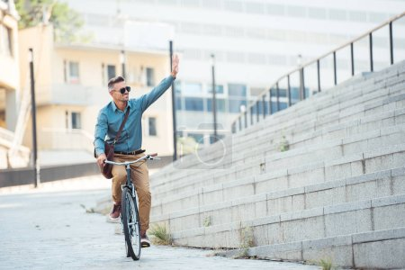 Photo for Smiling man in sunglasses riding bicycle and waving hand on street - Royalty Free Image