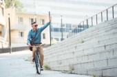 smiling man in sunglasses riding bicycle and waving hand on street