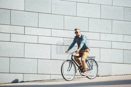 Photo for Handsome stylish man in sunglasses riding bicycle on street - Royalty Free Image