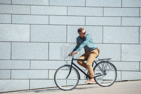 Photo for Side view of stylish middle aged man riding bicycle and looking over shoulder on street - Royalty Free Image