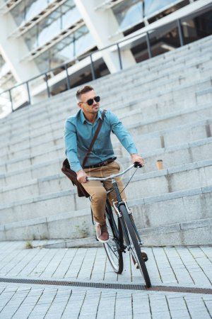 stylish middle aged man in sunglasses riding bicycle on street