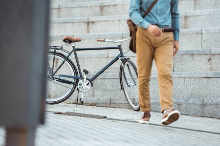 low section of stylish man walking on street, parked bicycle behind