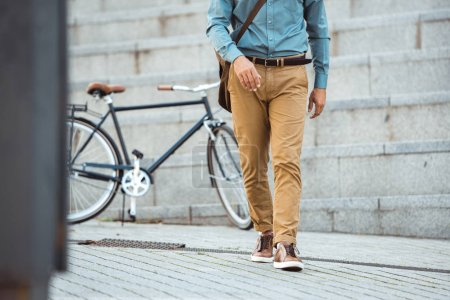 cropped shot of stylish man walking on street, parked bicycle behind
