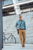 handsome middle aged man in sunglasses smiling at camera while walking on street, bicycle behind