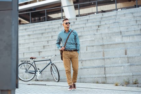 Photo for Handsome middle aged businessman in sunglasses walking on street, bicycle on background - Royalty Free Image