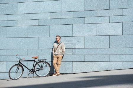 Photo pour Bel homme d'âge moyen en lunettes de soleil debout avec les mains dans les poches près du vélo et regardant loin sur la rue - image libre de droit