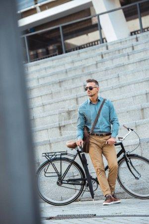 Photo pour Bel homme d'affaires âgé moyen dans lunettes de soleil avec parapluie tout en se tenant près de bicyclette sur la rue - image libre de droit