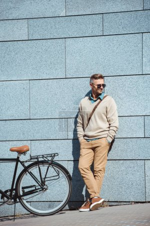 Photo for Stylish middle aged man in sunglasses standing with hands in pockets near bicycle on street - Royalty Free Image
