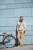 stylish middle aged man in sunglasses standing with hands in pockets near bicycle on street