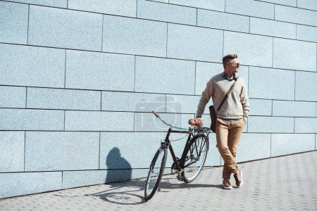 stylish middle aged man standing with bicycle and looking away on street