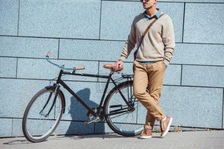 Foto de Tiro cortado de elegante hombre envejecido medio pie con bicicleta en la calle - Imagen libre de derechos