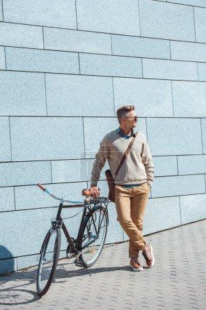 Foto de Con estilo hombre envejecido medio en gafas de sol que se inclinan en bicicleta y mirando lejos en la calle - Imagen libre de derechos