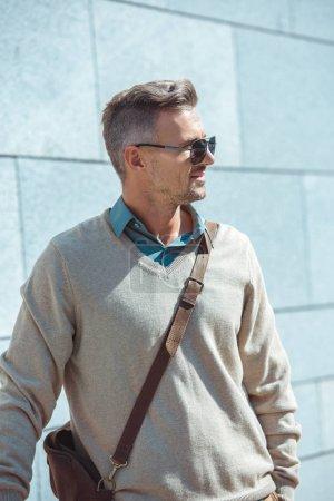 Foto de Retrato de guapo elegante medio de años hombre en gafas de sol mirando lejos en la calle - Imagen libre de derechos