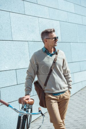 handsome middle aged man in sunglasses leaning at bicycle and looking away on street