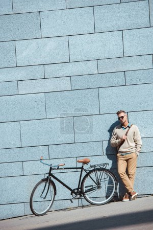 Photo for Handsome stylish middle aged man in sunglasses standing near bicycle on street - Royalty Free Image