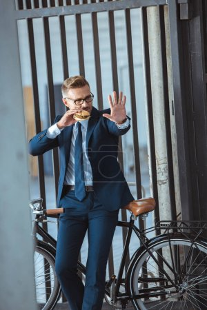 middle aged businessman gesturing by hand while sitting on bicycle and eating burger on street