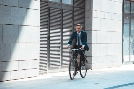 middle aged businessman in suit and eyeglasses riding bicycle on street