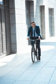 handsome middle aged businessman in suit and eyeglasses riding bicycle on street