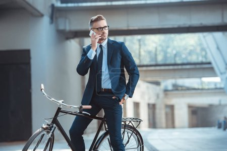 handsome businessman sitting on bike and talking by smartphone on street