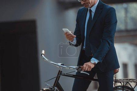 Photo pour Recadrée tir d'homme d'affaires assis sur le vélo et l'utilisation de smartphone - image libre de droit