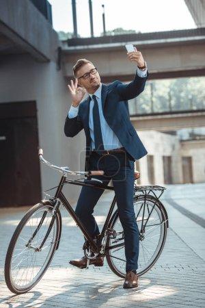 Foto de Empresario sonriente mostrando signo ok para smartphone sentado en bicicleta en la calle - Imagen libre de derechos