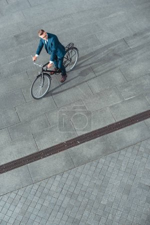 high angle view of handsome businessman in formal wear sitting on bike and looking away