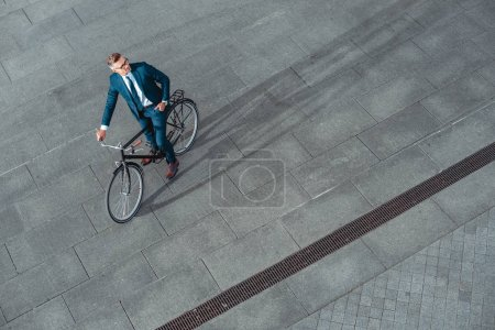 Photo pour Vue d'angle élevé de bel homme d'affaires en costume et lunettes assis sur le vélo et à la recherche de suite - image libre de droit