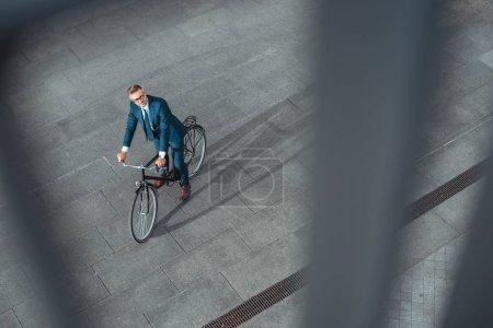 Foto de Vista de ángulo alto guapo medio empresario de traje y gafas bicicleta - Imagen libre de derechos